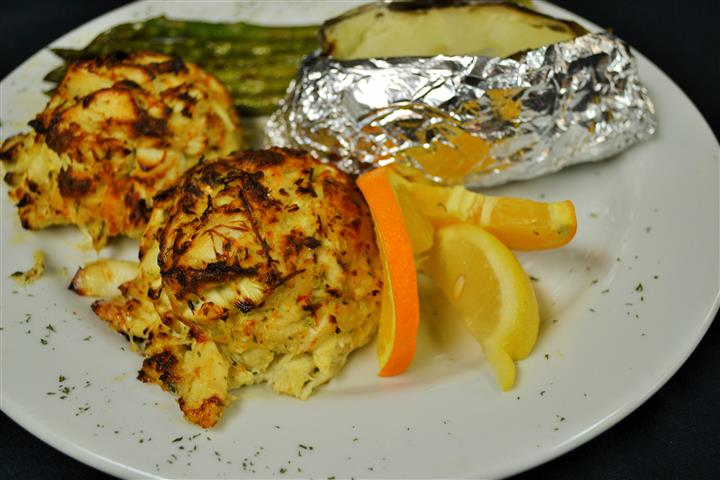 Crab cakes served with jacket potato and asparagus