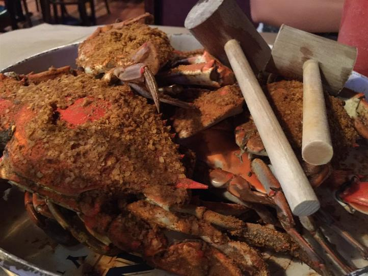 Crabs served on a metal platter served with two hammers