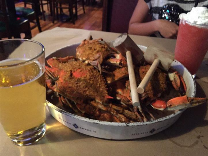 Crabs served on a metal platter served with two hammers and a glass of beer