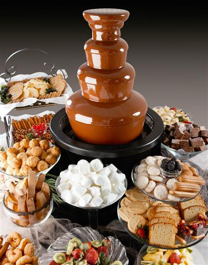 A chocolate fountain surrounded with a variety of catering dishes
