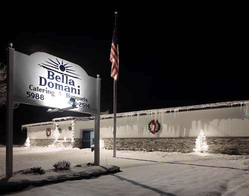 An outdoor shot of the sign of Bella Domani Catering next to the US flag, in a snowy winter night