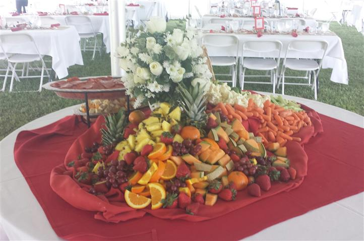 A round buffet with a variety of fresh fruit and vegetalbes
