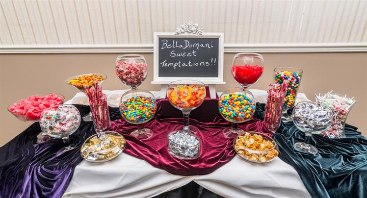 "A buffet with a variety of sweets and a blackboard with the text ""Bella Domani Sweet Temptations!!"""