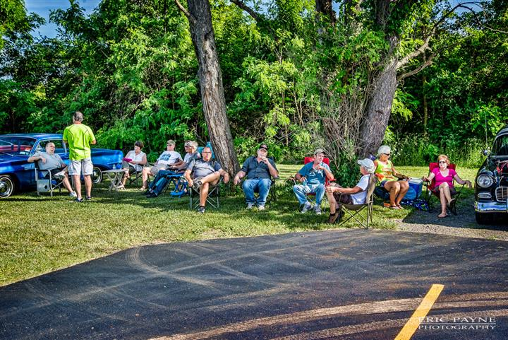 Photo of people sitting on foling chairs during the antique cars fest