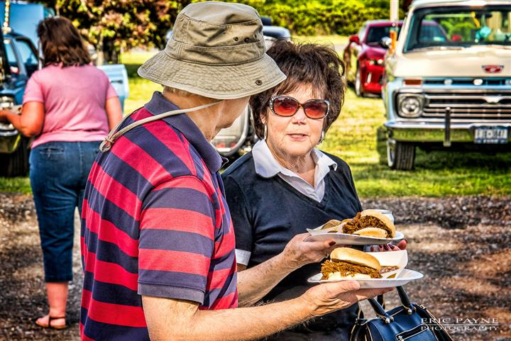 A couple holding pull pork burgers