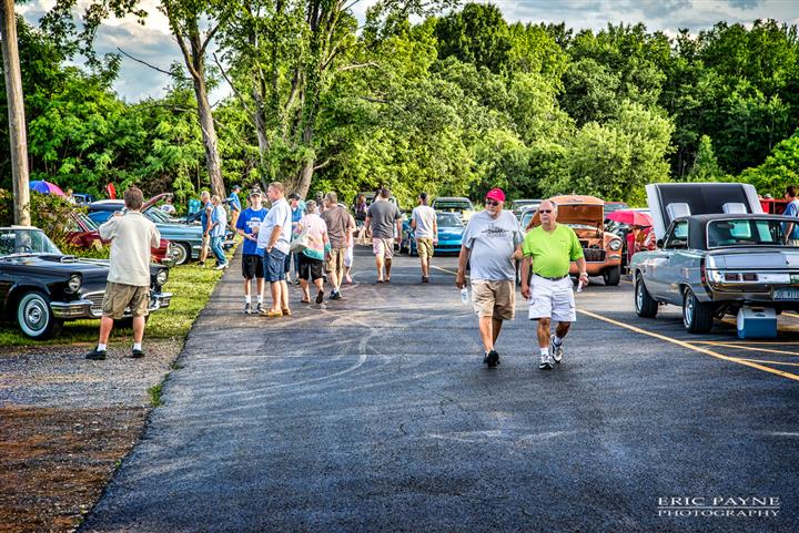Men walking among the antique cars collection