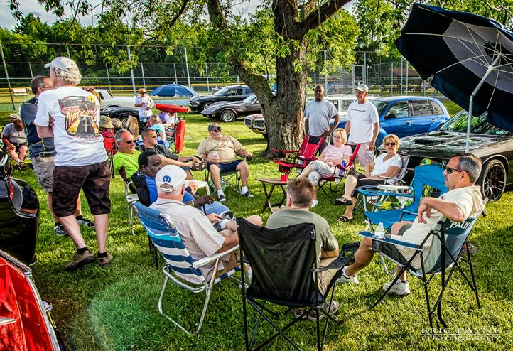 Outdoor shot of people sitting on foling chairs during the antique cars fest