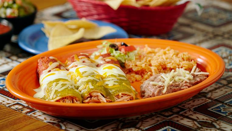 Enchiladas 3 soft corn tortillas wrapped around meat and cheese and then covered in the sauce of your choosing and even more cheese