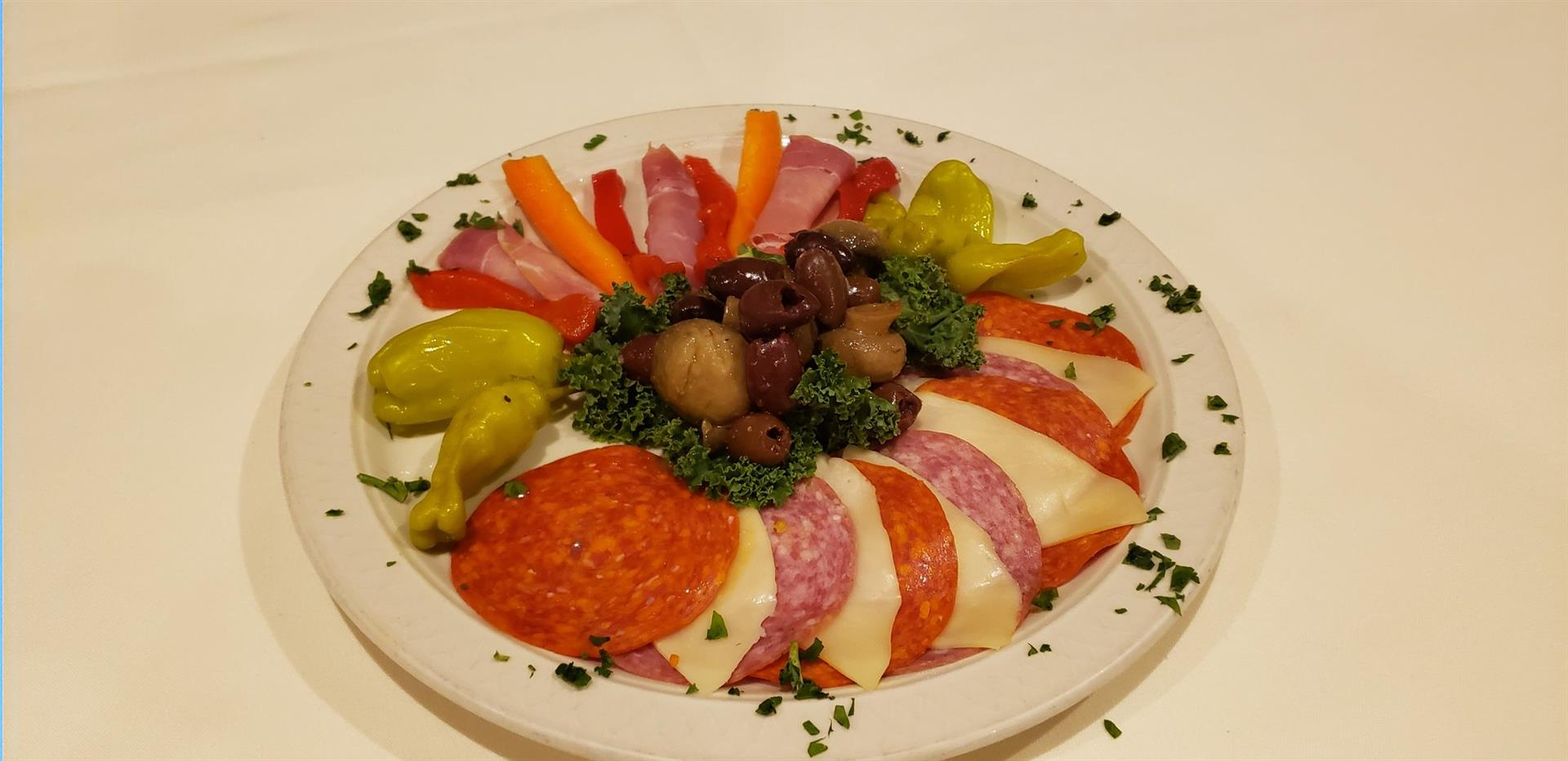 Cold antipasti with assorted sliced meats, cheeses, olives and peppers