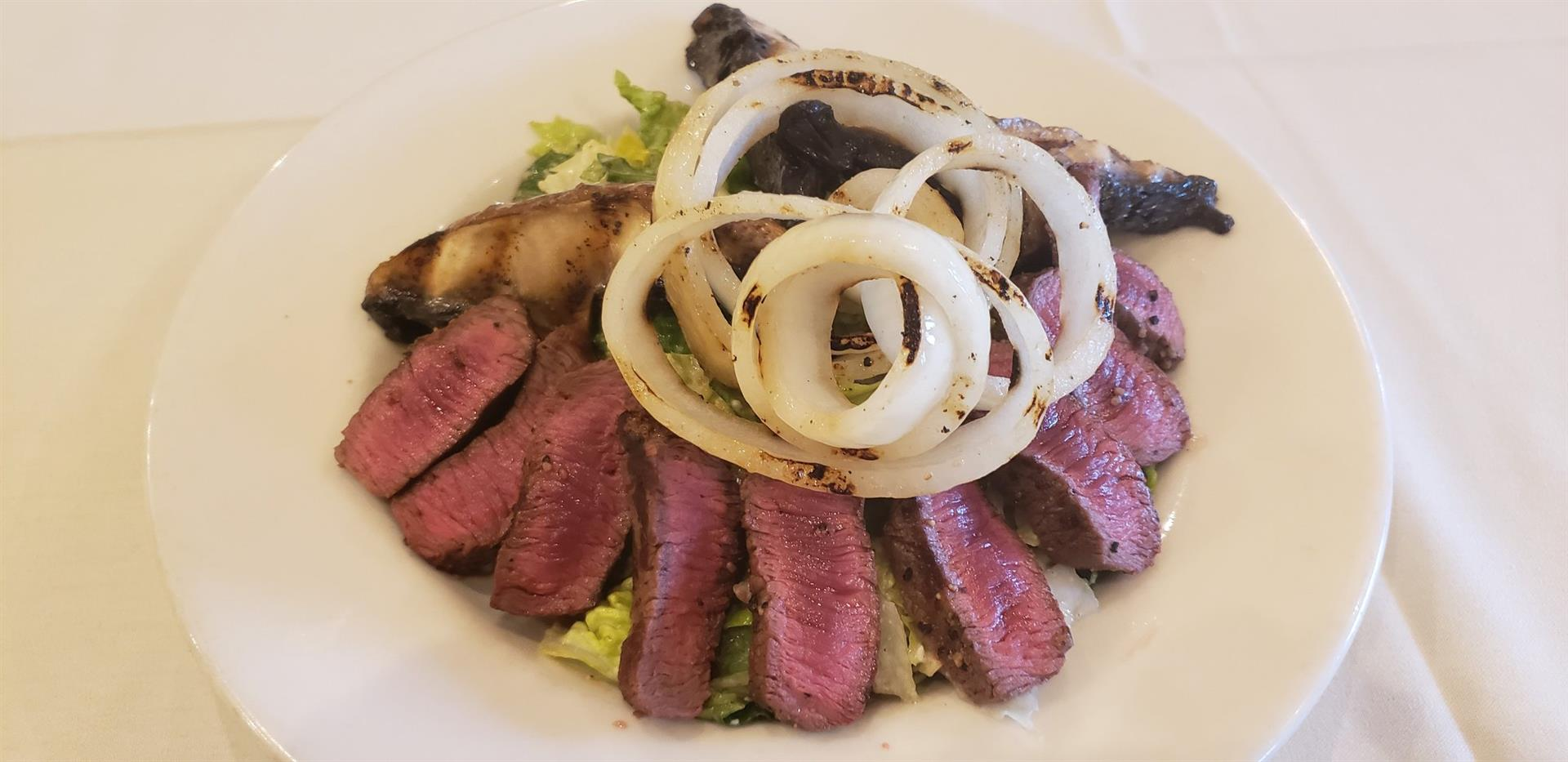 Sliced filet mignon salad with grilled onions