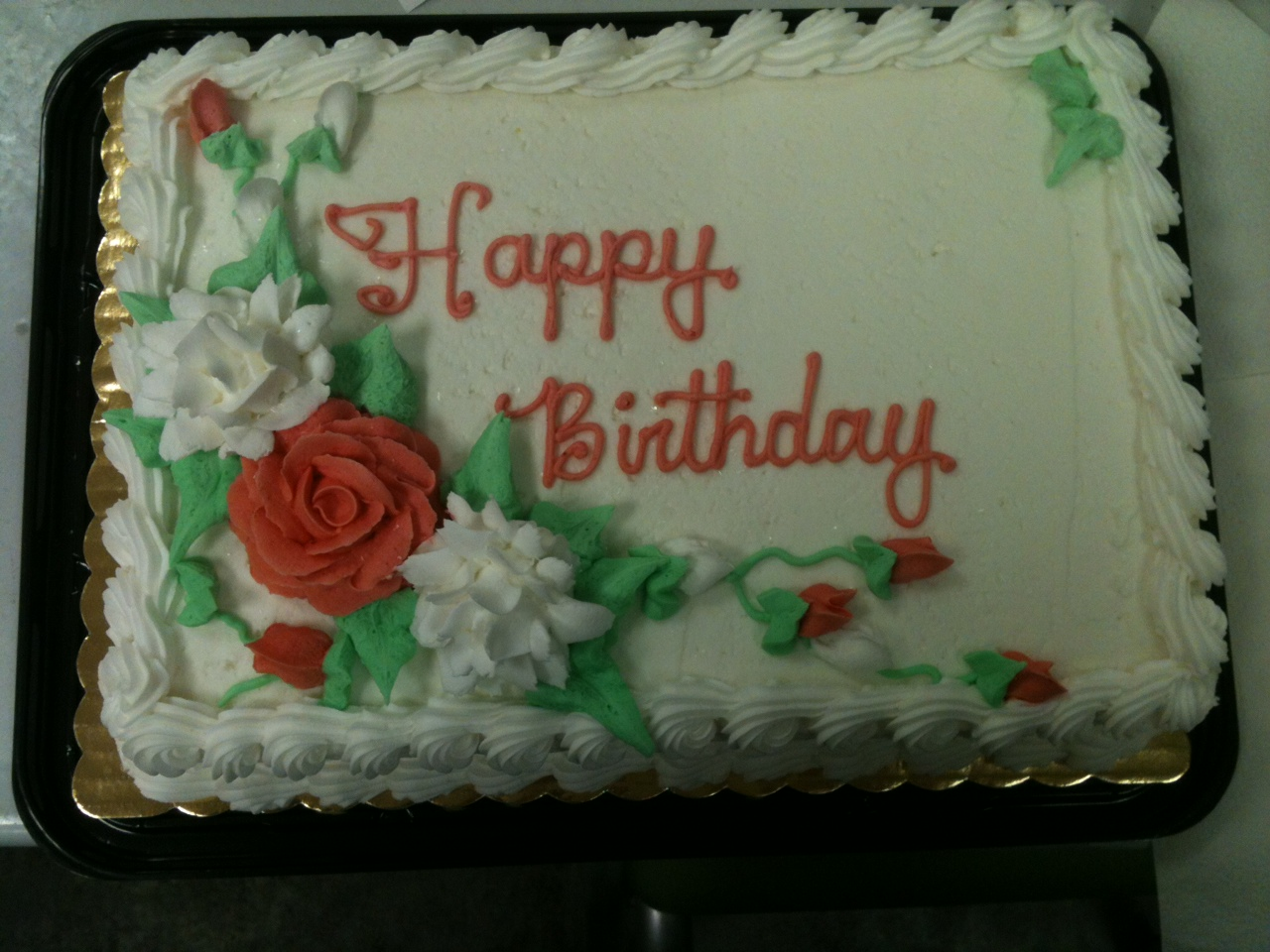 rectangle cake with Happy Birthday writen on it with flowers clustered in the bottom left corner