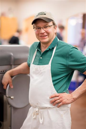 a man smiling at the camera with an apron on