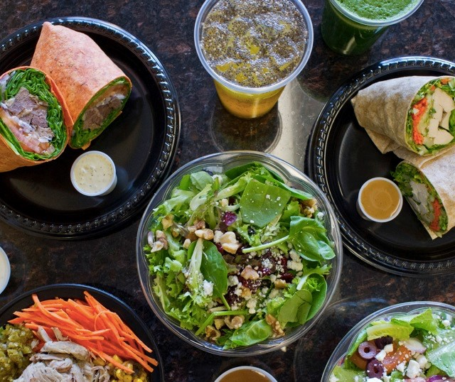 assorted salads, wraps, and teas on marble table