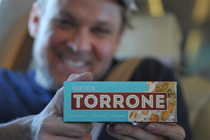 man smiling holding a torrone box