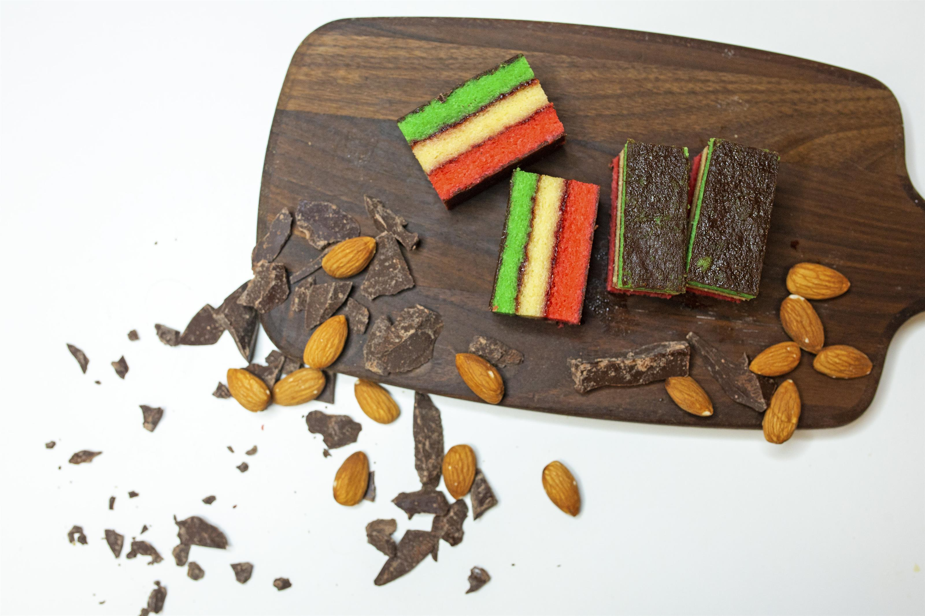 rainbow cookies on a wood board with chocolate pieces and almonds