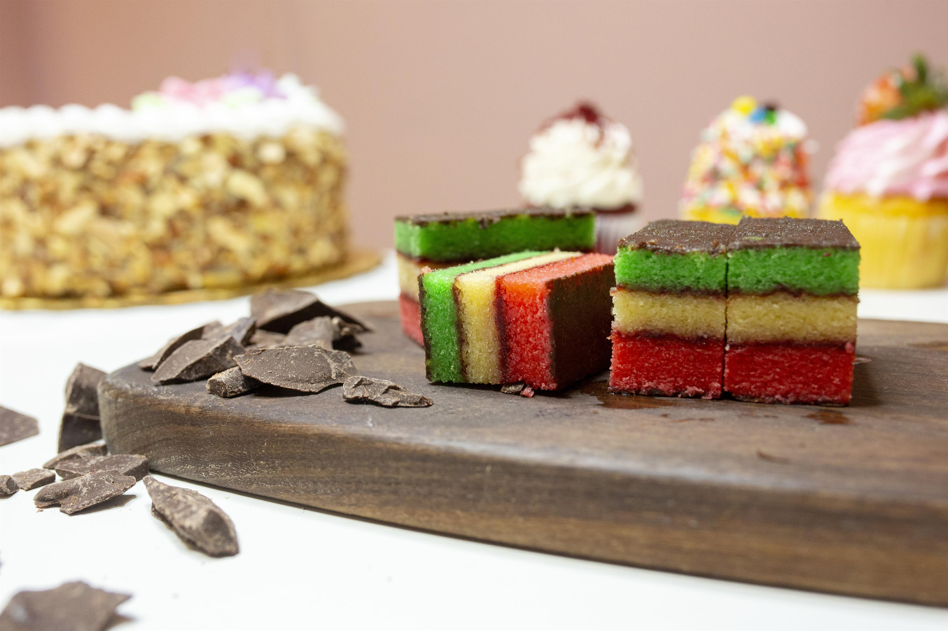 rainbow cookies on a wood board with chocolate pieces