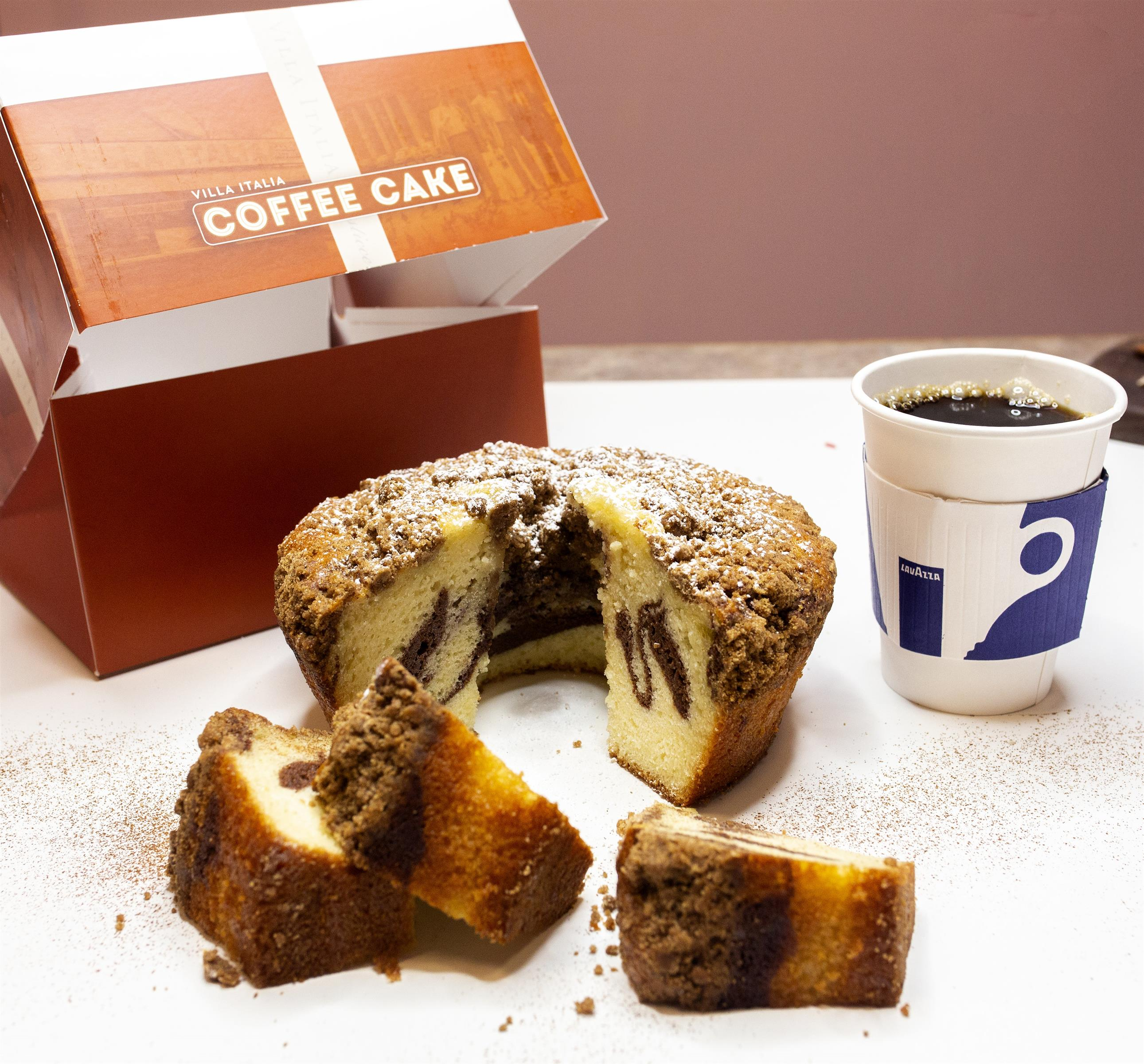 cake with slices taking out next to a cup of coffee and an  emtpy box