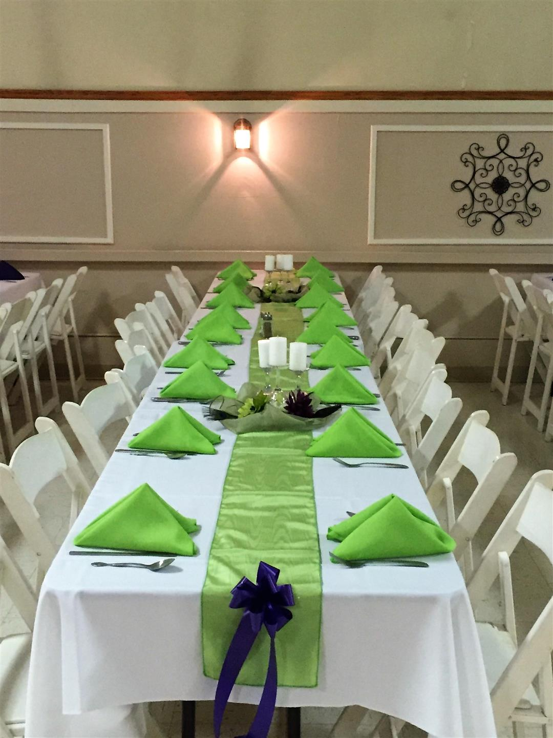long table setup with tablecloths, folded napkins and ribbon decorations with candles