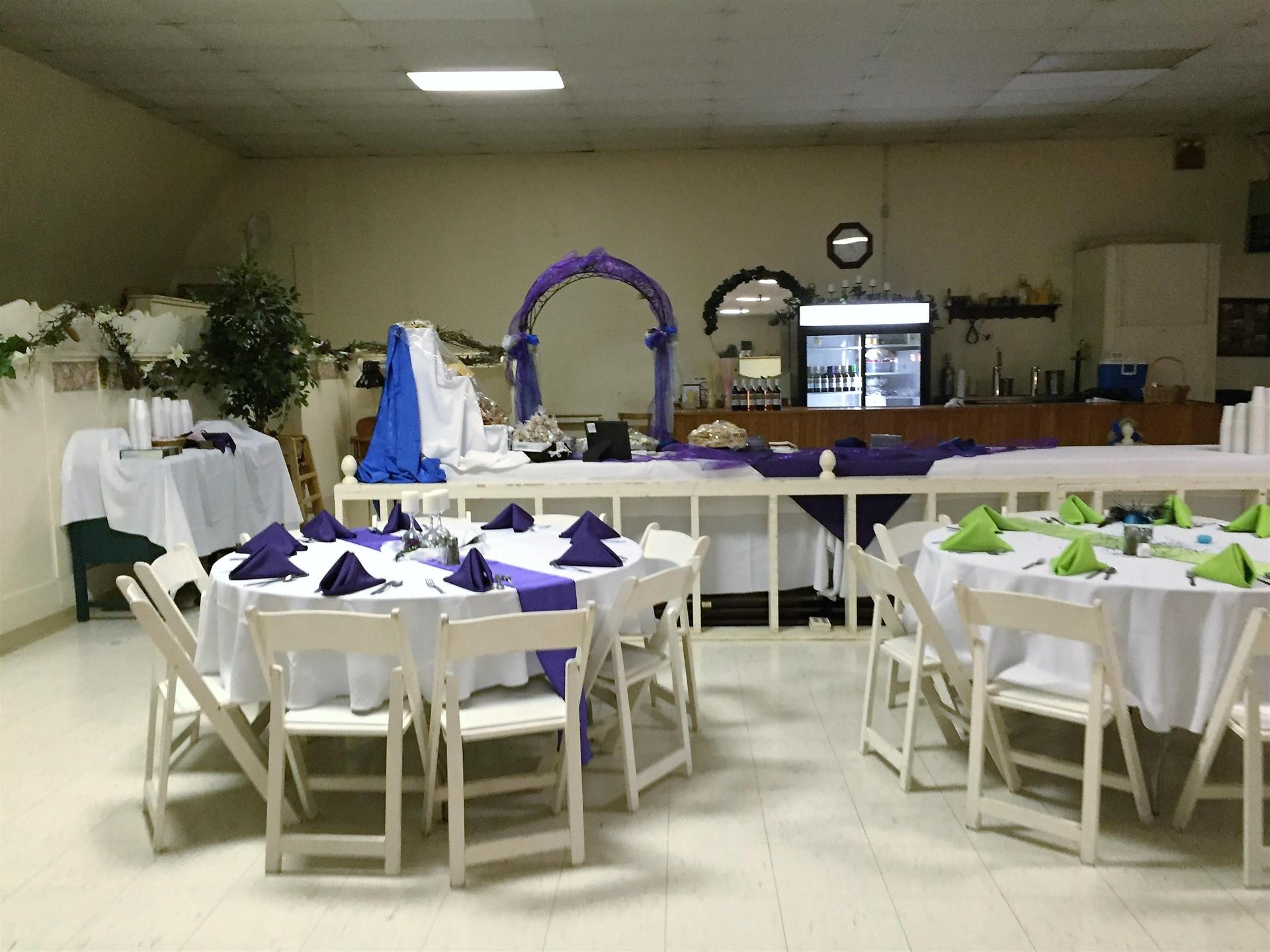 set of circular tables setup with tablecloths, folded napkins and ribbon decorations
