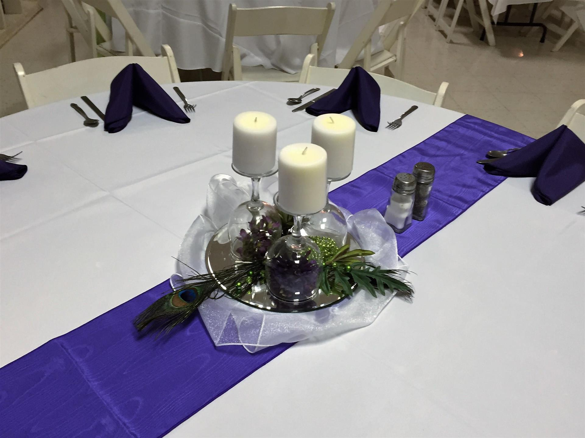 circular table with a tablecloth, folded napkins and a floral centerpiece with candles