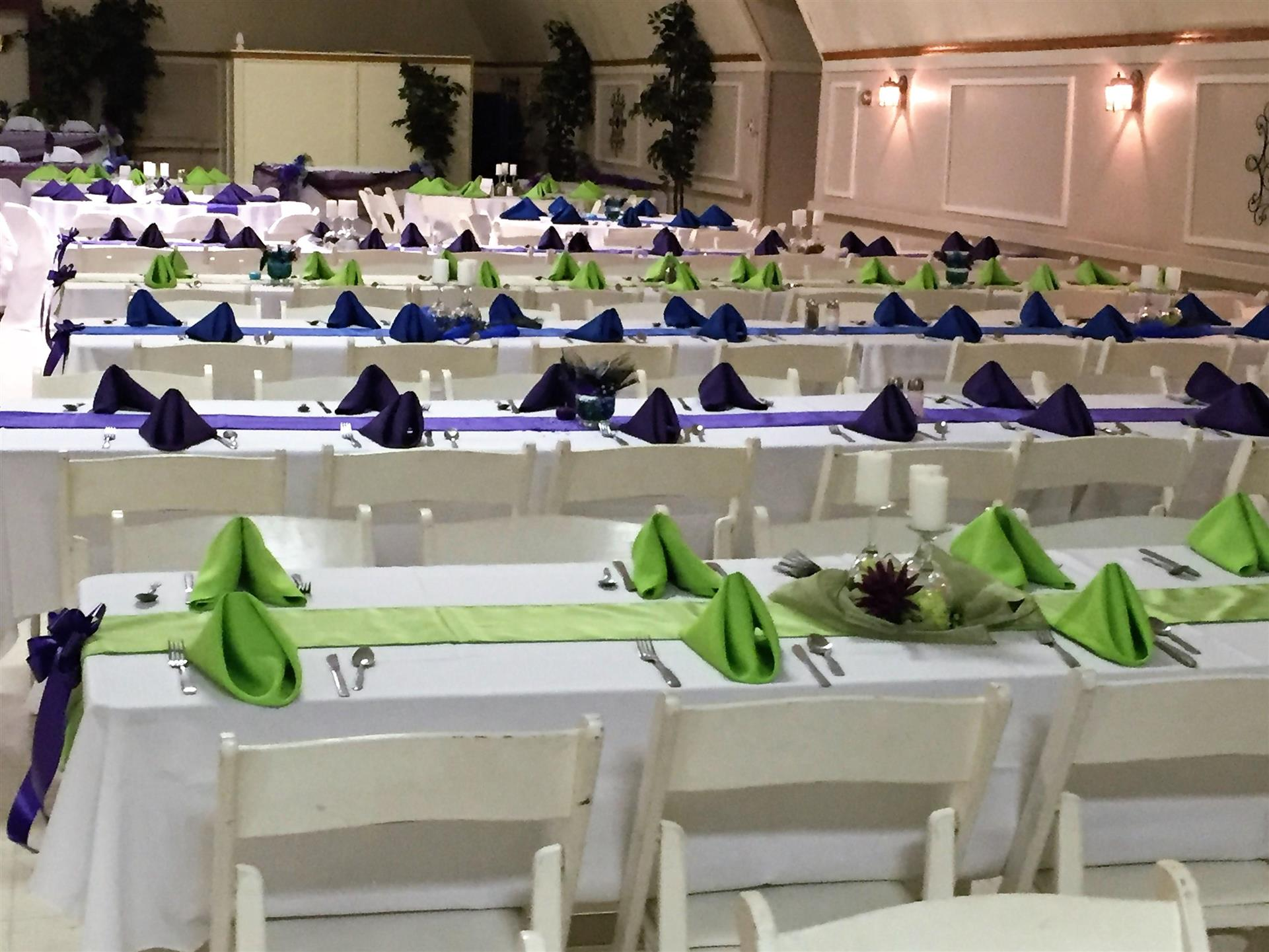 set of long tables setup with tablecloths, folded napkins and ribbon decorations