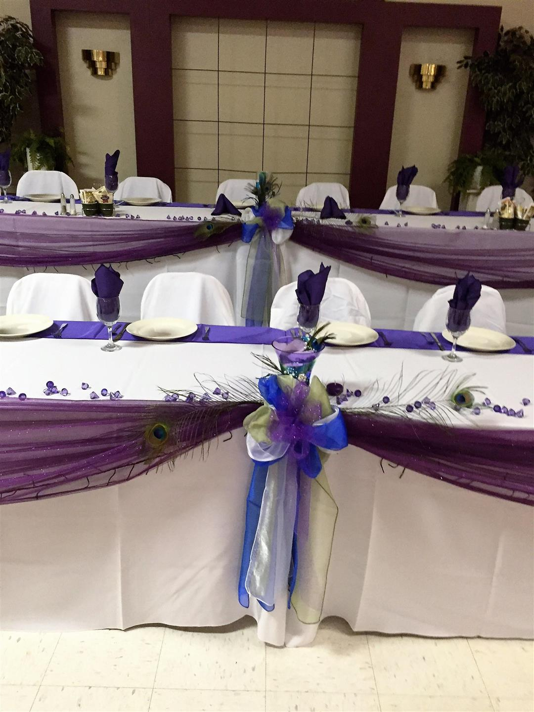 set of long tables setup with tablecloths, napkins in glasses and ribbon decorations