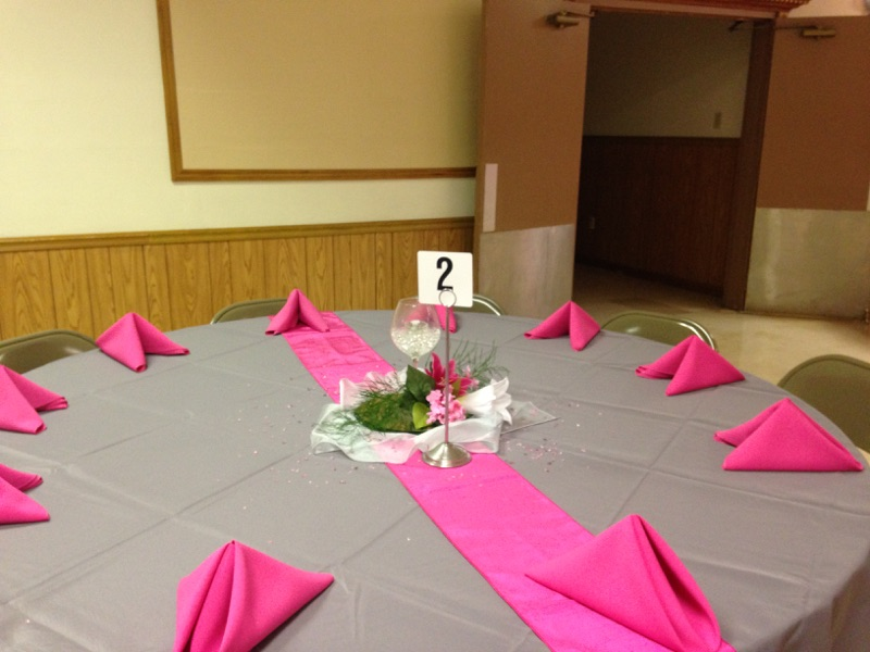 circular table with a tablecloth, folded napkins and a floral centerpiece