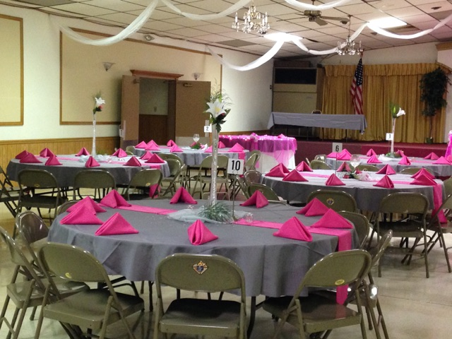 catering hall setup with circular tables, chairs, tablecloths and folded napkins