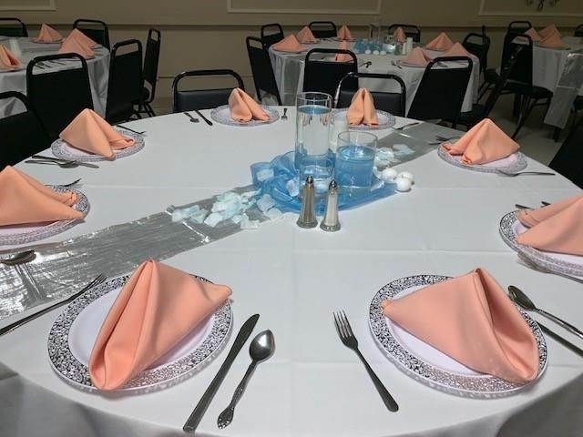 circular table with a tablecloth, folded napkins and candles as centerpieces