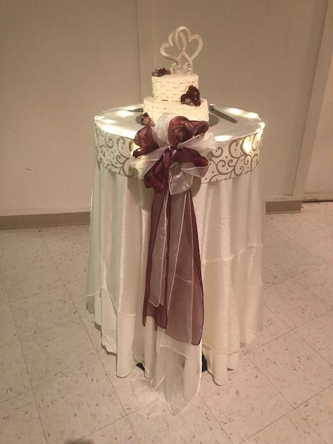 Wedding cake displayed on a table covered with cloth and decor