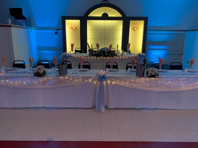 set of tables with a tablecloth, folded napkins and candles as centerpieces