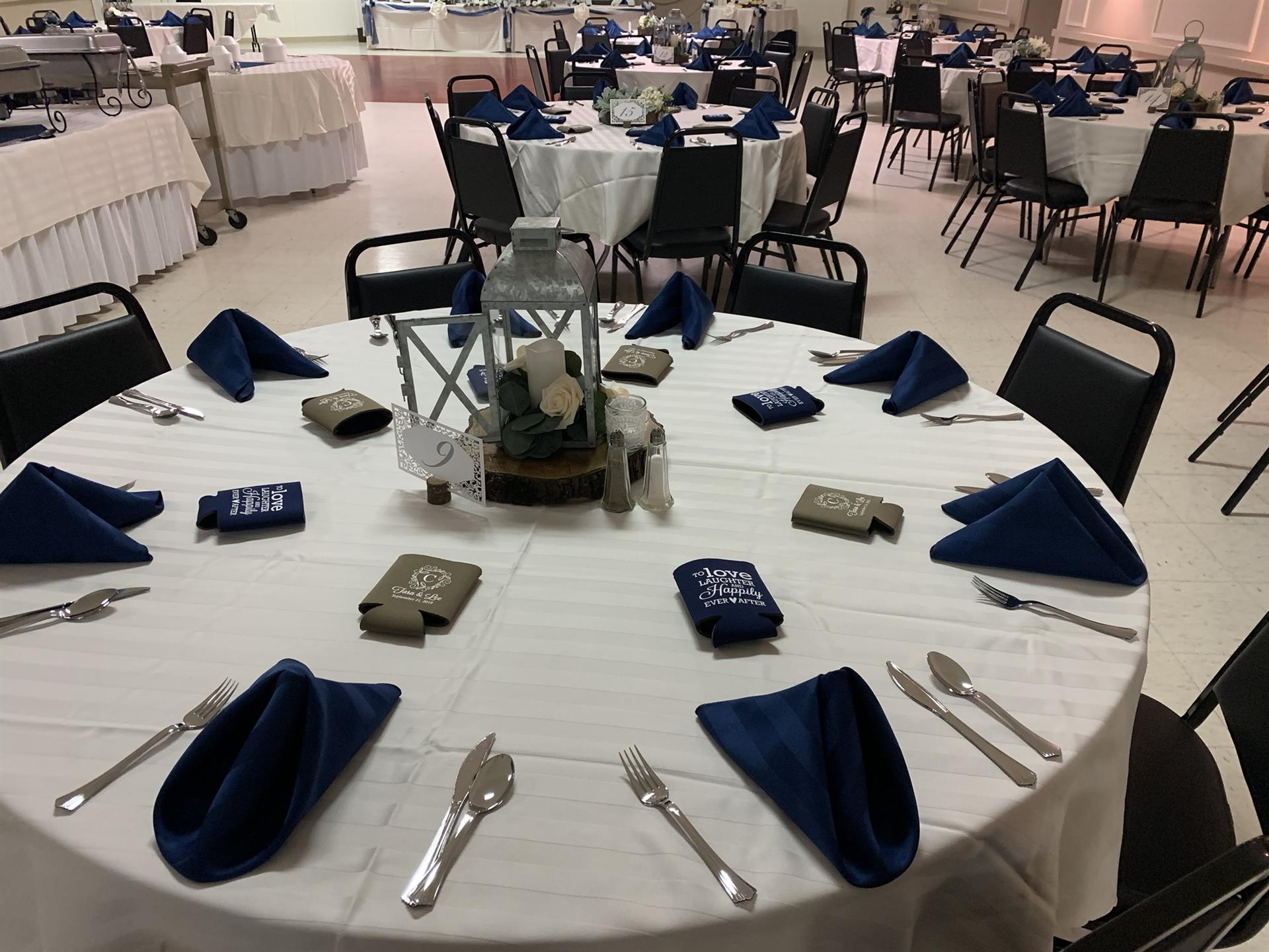 A round table set with napkins and silverware.