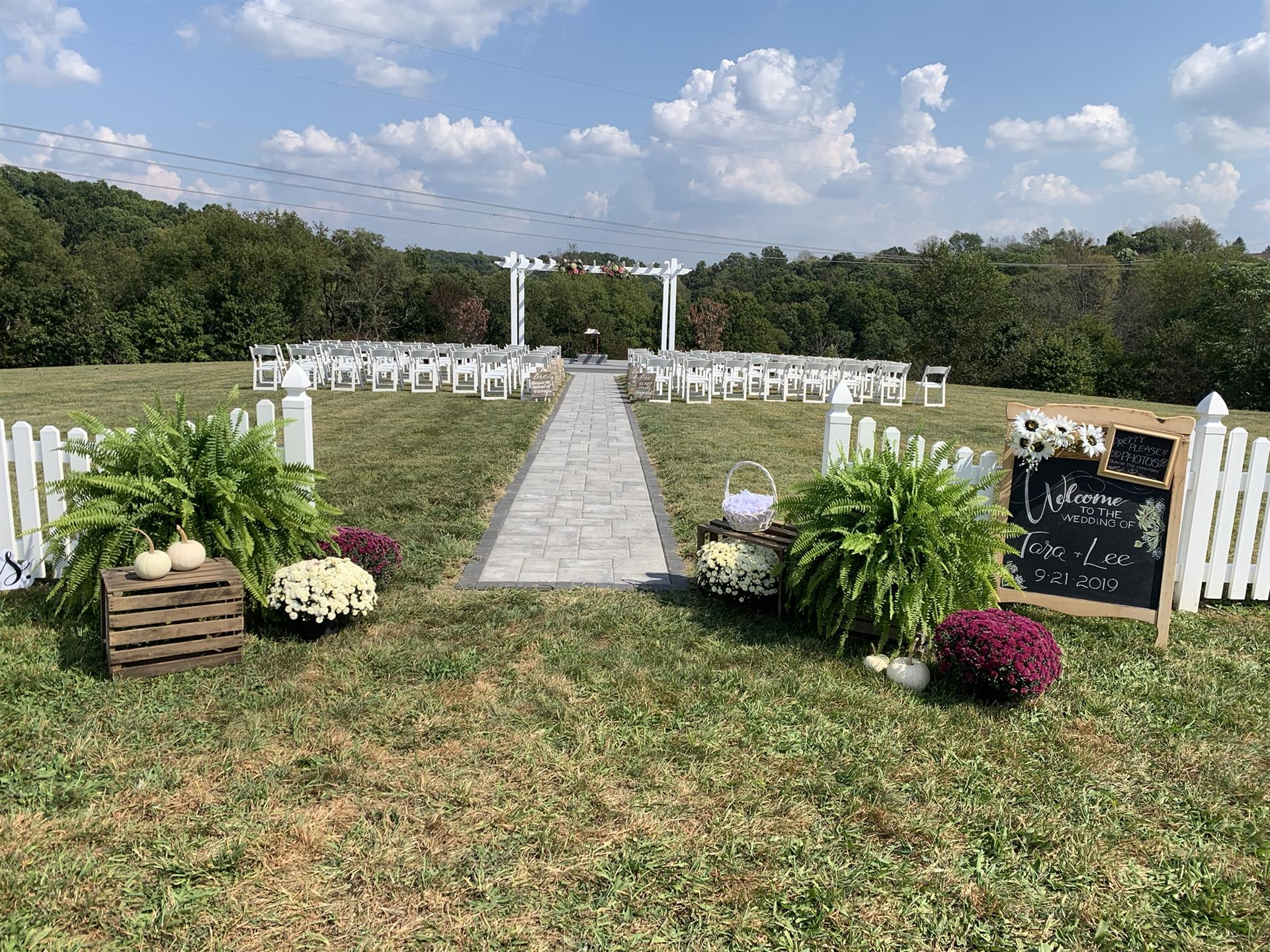 An isle for a wedding reception with white folding chairs and flowers.