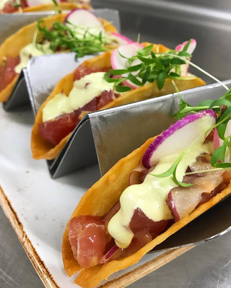 Fish tacos topped with radishes and a sauce