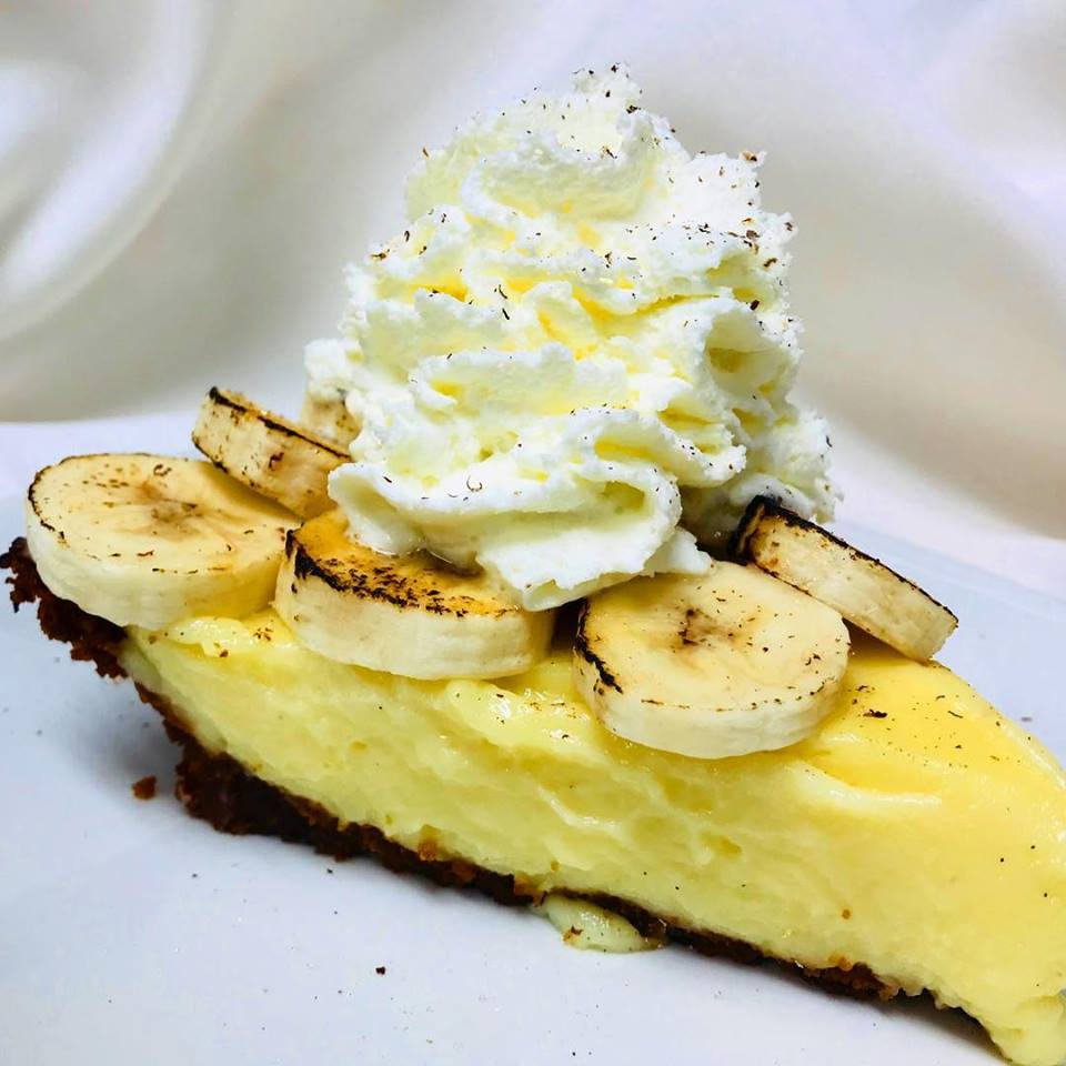Banana cheesecake with banana slices and whipped cream on top