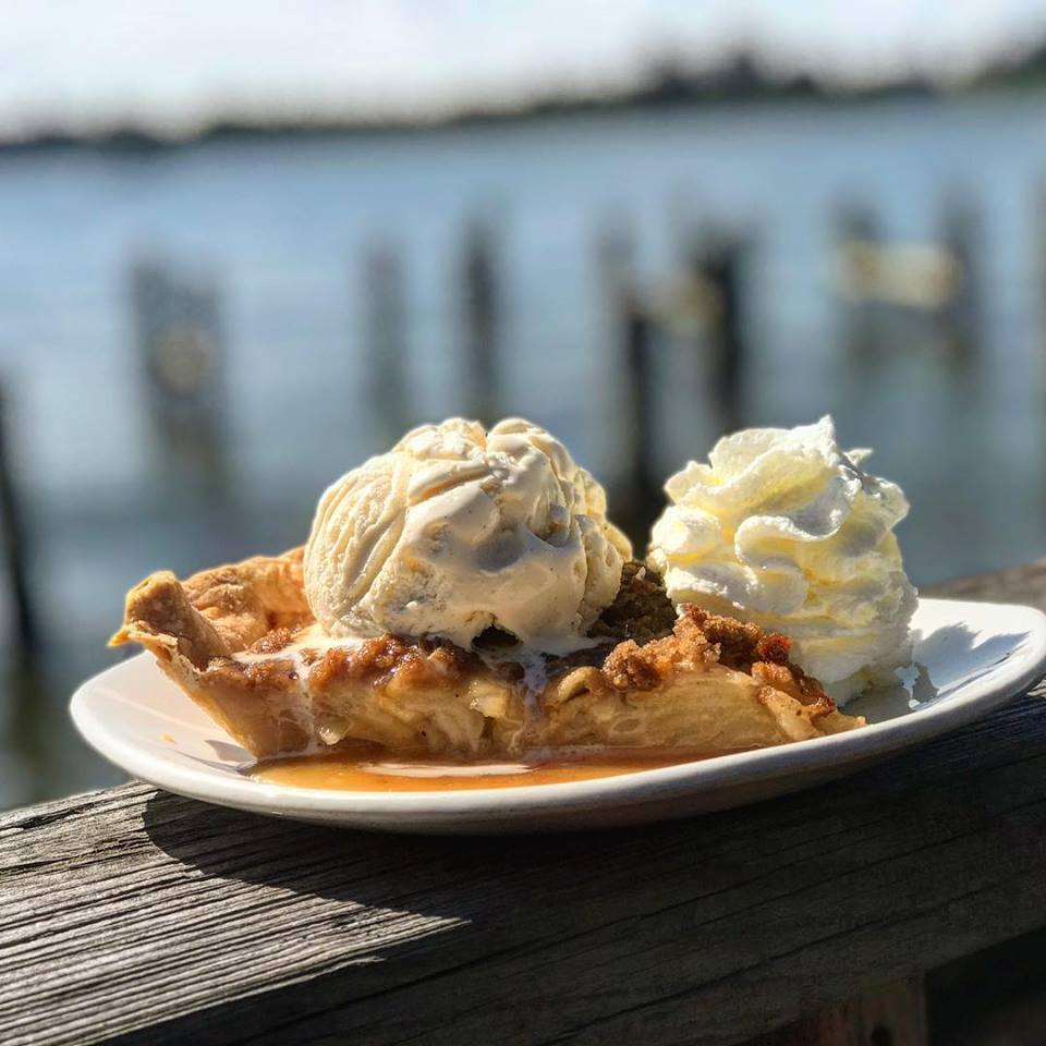 Apple pie topped with ice cream on a white place with a harbor in the background