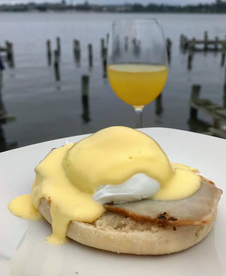 Eggs Benedict on a plate with a mimosa in the background