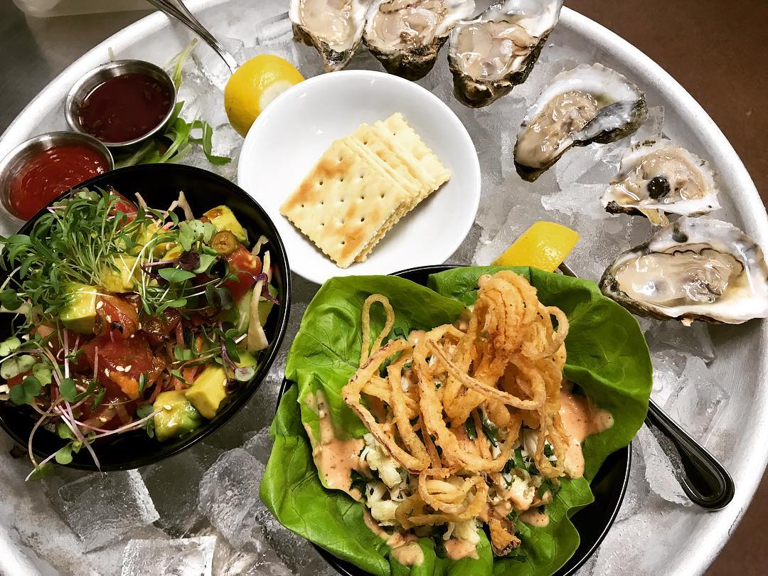 Oysters in an ice dish with a side of crackers, salad, and fried onion straws