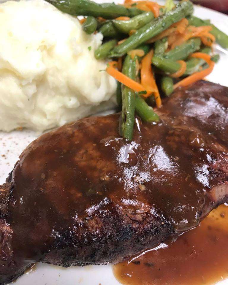 Steak with gravy and a side of mashed potatoes and string beans