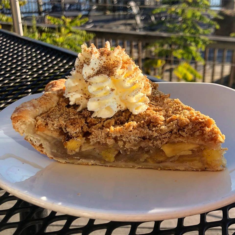 Apple pie topped with whipped cream on a plate outside