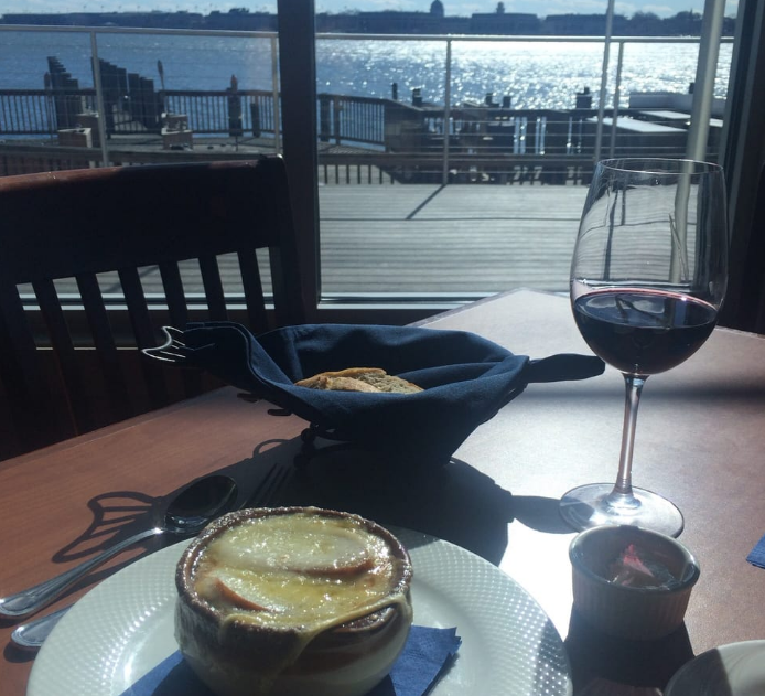 French onion soup on a table with a glass of wine and view of the water