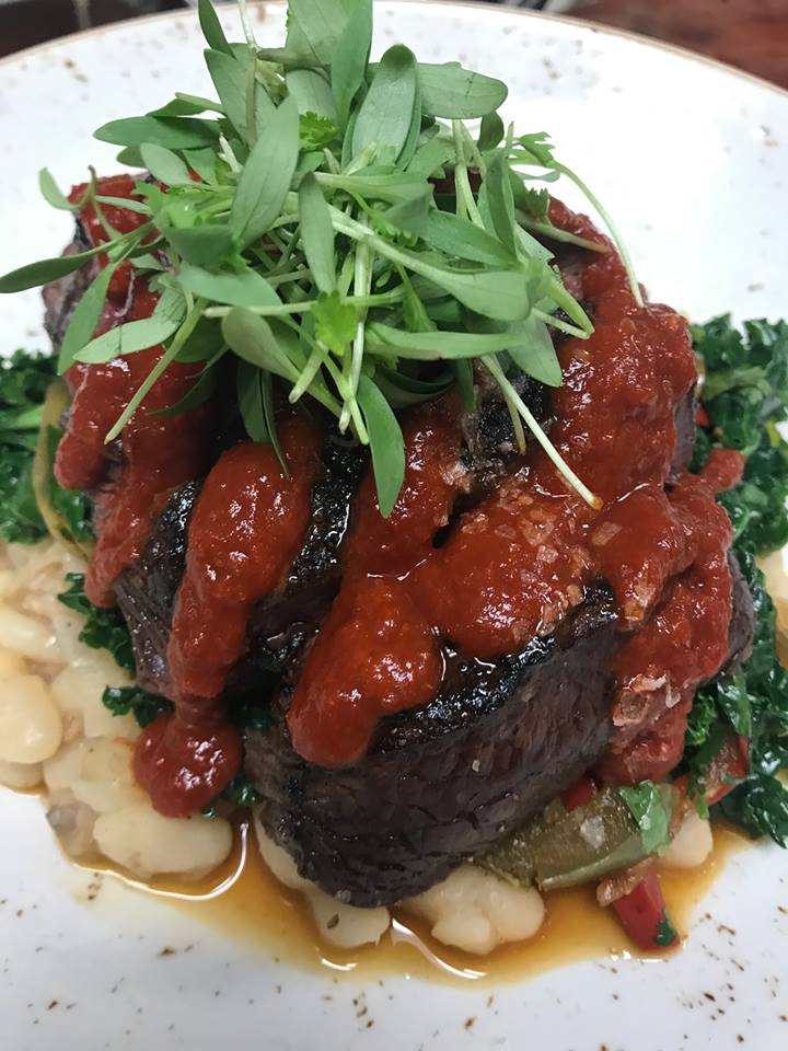 Steak topped with a red sauce and arugula