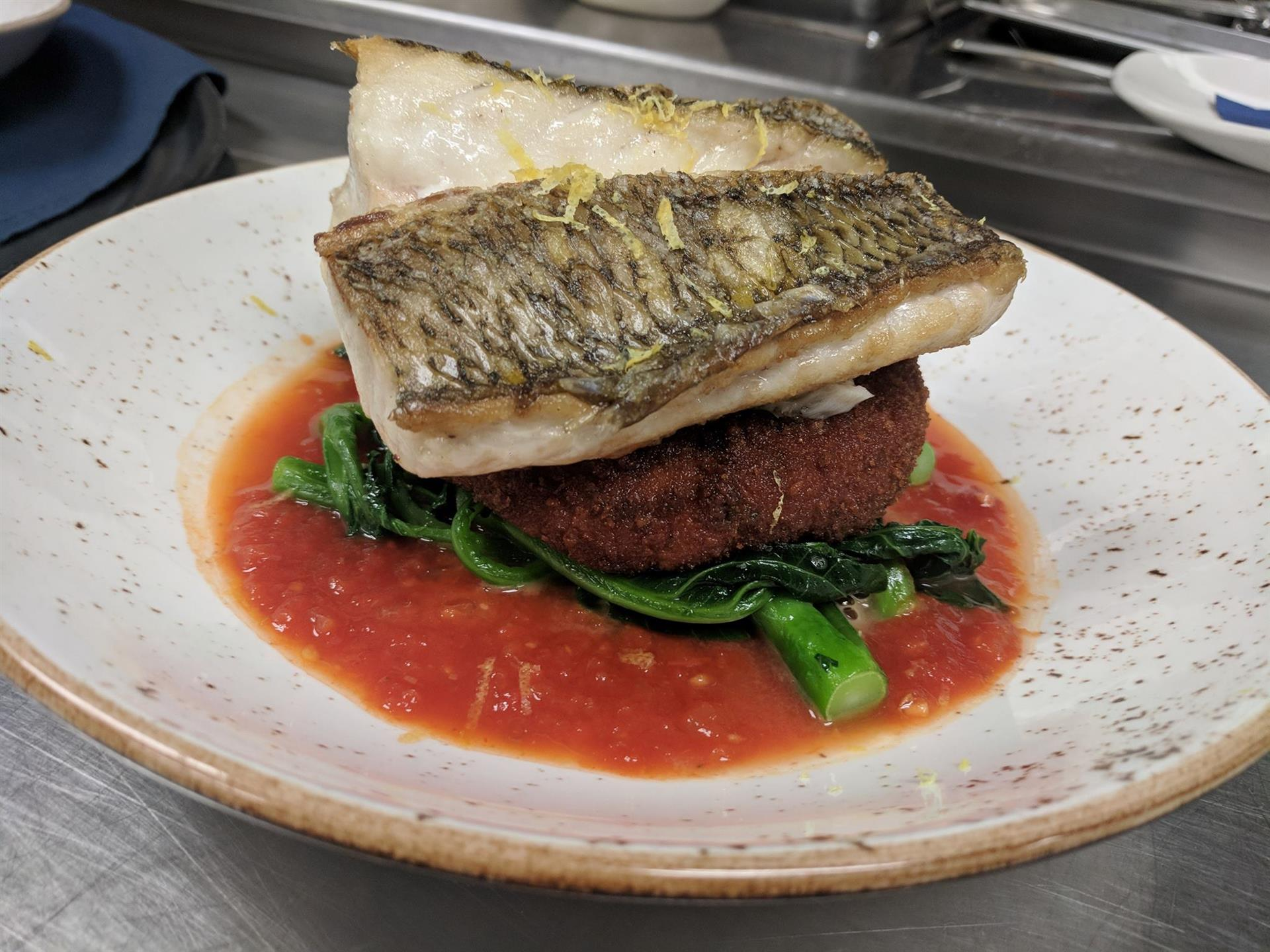 Fish over a red sauce on a white plate