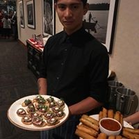 a waiter holding a platter of appetizers
