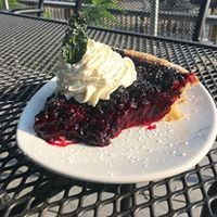 piece of pie with whipped cream on top sitting on an outdoor table
