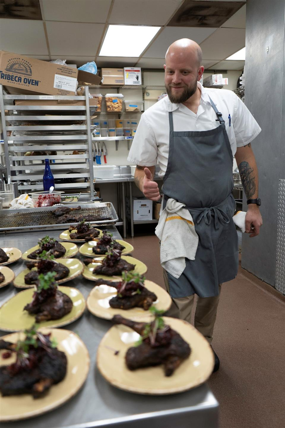 a chef giving a thumbs up to many plates of duck legs