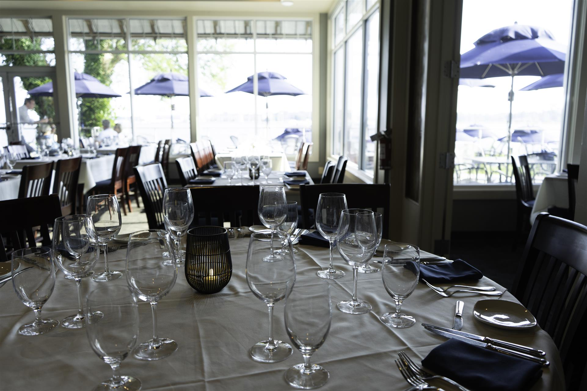 a white table cloth table with wine glasses and napkins