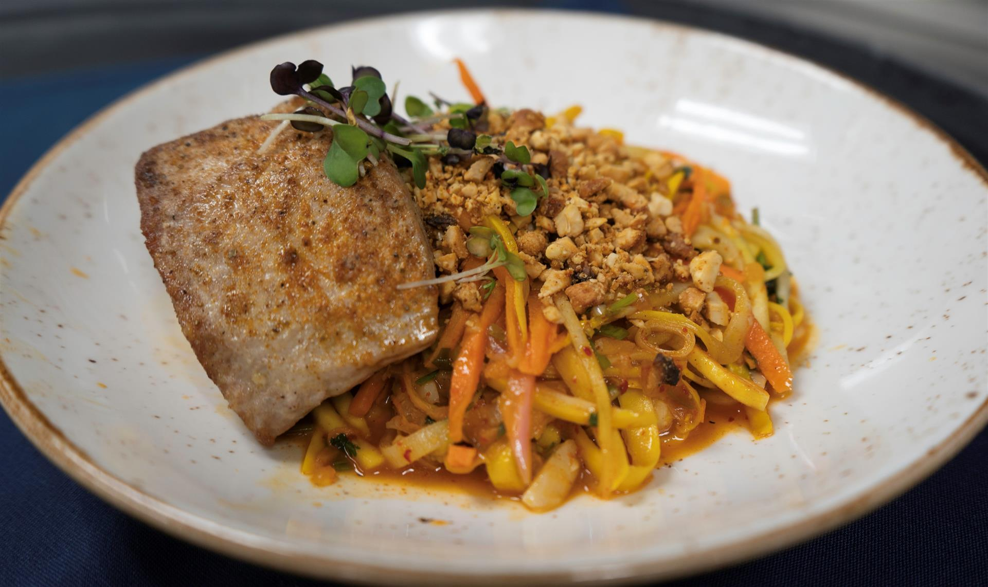 fish with linguine, mixed vegetables, and nuts