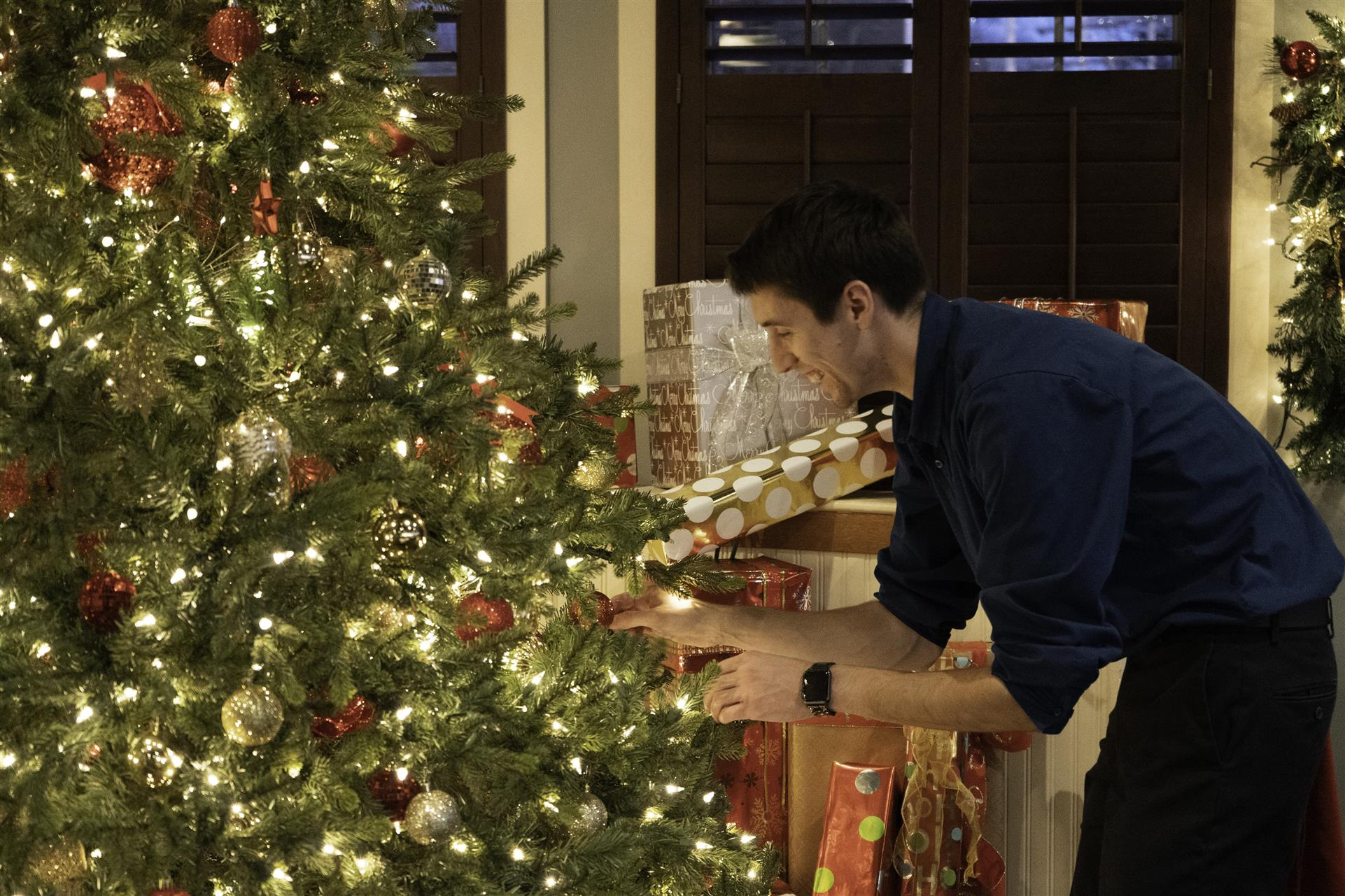 man putting ornament on a christmas tree