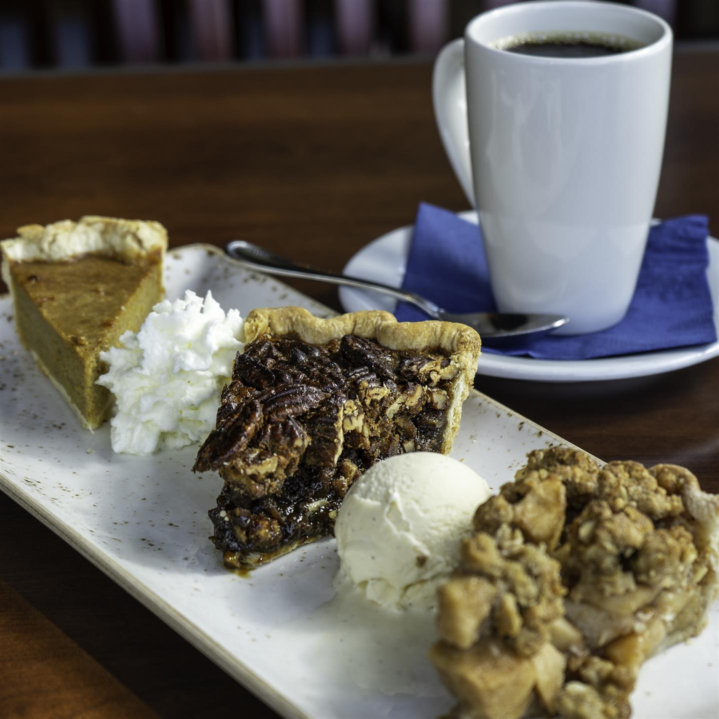 a slice of pumpkin, pecan, and apple pie on a tray with a side of coffee